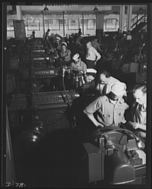 In the tool and die building at the River Rouge plant, vast facilities are being used to train personnel for the U.S. Navy. Here naval cadets are being instructed in lathe operation by the skilled instructor- mechanics