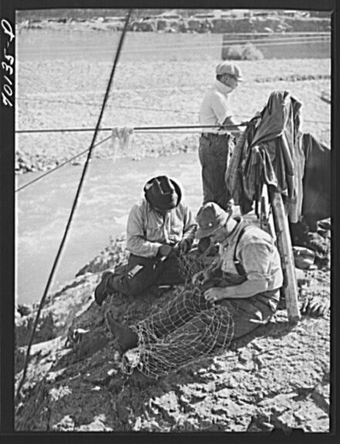 Indian fishermen repairing their nets. Celilo Falls, Oregon. The salmon run was on and fishermen took salmon and sold them to commercial canneries