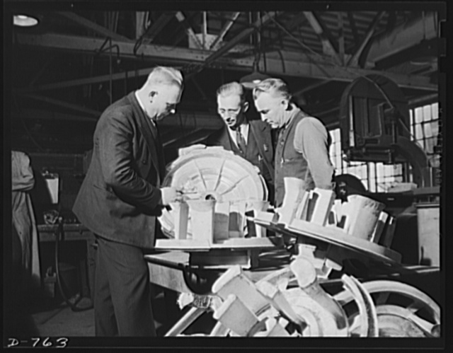 Inspection of a magnesium casting. This one is a crank case blower for an aircraft engine, and is being inspected here before being delivered to the machine shop for finishing. Ford River Rouge plant