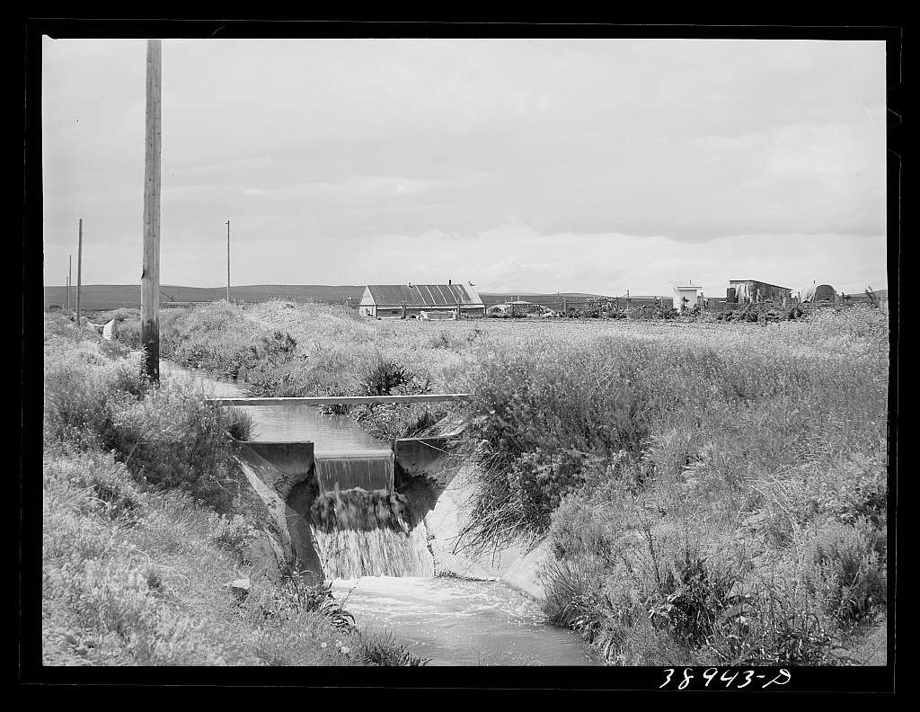 Irrigation ditch and gate with the Free family farmstead in the background. This family is a FSA (Farm Security Administration) rehabilitation borrower. Dead Ox Flat, Malheur County, Oregon
