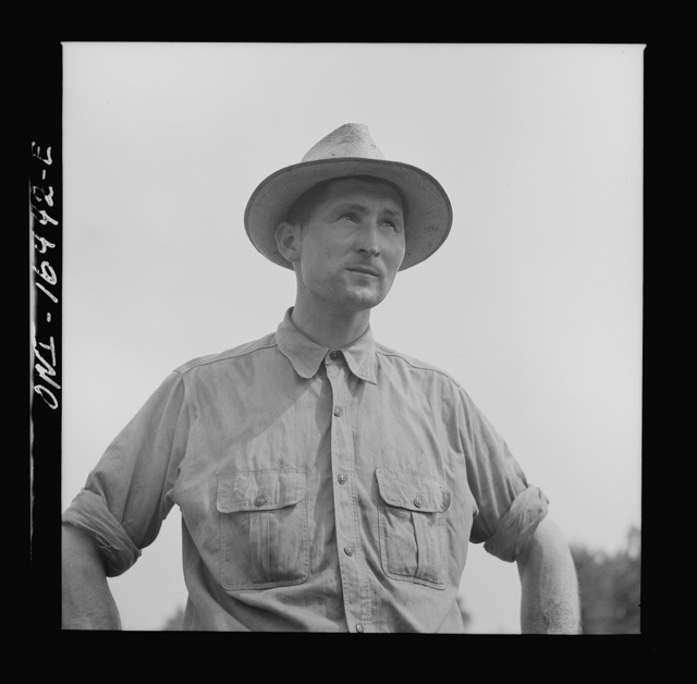 Jackson, Michigan. Soldier, who was granted a furlough to help with the harvesting on this farm, watching threshing