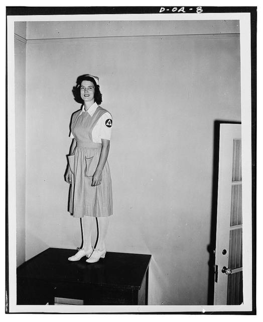 Jane Womack models new uniform selected for 100,000 defense volunteers to be trained as nurse's aides by the American Red Cross. The training project, in collaboration with the Office of Civilian Defense, is designed to relieve the acute shortage of nursing service threatening civilian hospitals and health agencies because of demand for nurses