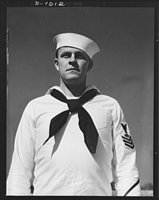 John Marshall Evans, Radioman, first class. Radioman Evans' uniform is the white service dress worn both aboard the ship and at shore station during the summer months or in the tropics. Naval Air Station, Anacostia, Washington, D.C. August 21, 1941