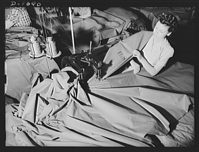 """Langdon Tent and Awning Company, Wichita, Kansas. With the grade and dexterity of master dressmaker this attractive young woman fabricates """"pup"""" tents for the expanding defense Army. A two-needle felling machine joins two widths of cloth to form the main body of the tent"""