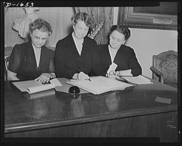 "Left to right: Mrs. Henrietta Nesbitt, White House housekeeper; Mrs. Roosevelt, Assistant Director of the Office of Civilian Defense: Harriet Elliott, Associate Administrator in charge of the Consumer Division, Office of Price Administration (OPA). Mrs. Roosevelt and Mrs. Nesbitt, took the ""Consumer Pledge for Total Defense"" drafted by Miss Harriet Elliott. The pledge reads: ""As a consumer, in the total defense of democracy, my country ready, efficient, and strong; I will buy carefully. I will take good care of the things I have. I will waste nothing"""
