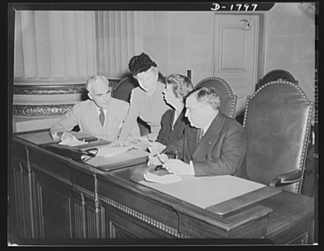 """Left to right: Paul V. McNutt, Federal Security Administrator; Miss Elise Davison, Assistant Director in Charge of Volunteer Activities, Women's Division, Office of Civilian Defense; Mrs. Roosevelt, Assistant Director, Office of Civilian Defense; Mayor F.H. LaGuardia, Director of Office of Civilian Defense, conferring at a conference on """"Women's Activities in Civilian Defense,"""" on November 8, 1941"""