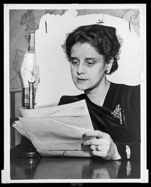 [Lisa Sergio, head-and-shoulders portrait, seated at table with microphone, facing front, holding papers] / World Telegram photo by Edward Lynch.