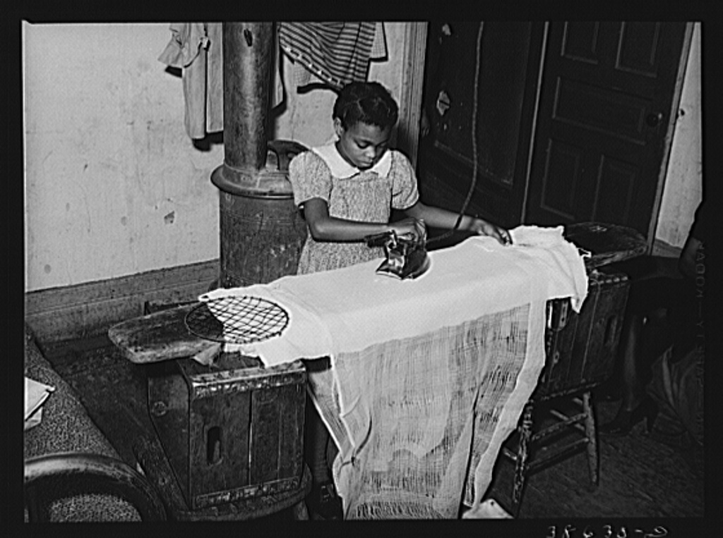 Little girl ironing. Family is on relief. Chicago, Illinois