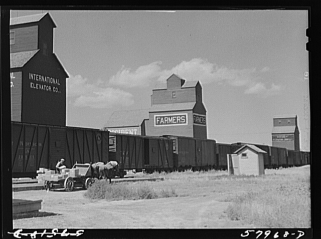 Loading freight on to wagon from station platform as the freight train is leaving Homestead, Montana