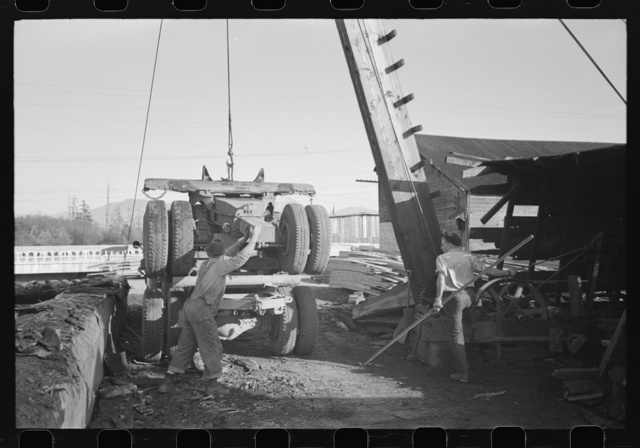 Loading onto trailer truck, logging operations, Tillamook County, Oregon. The trailer is carried on the truck when it returns to the woods empty for more logs