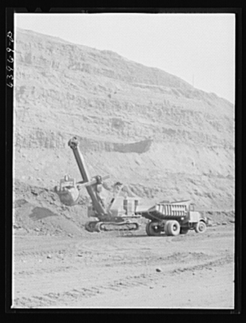 Loading truck with iron ore at the Albany mine near Hibbing, Minnesota. Use of trucks was initiated in this mine two years ago and railroad tracks removed