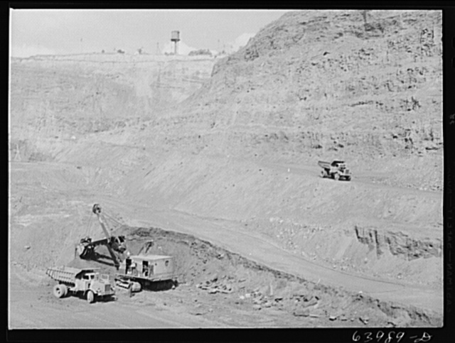 Loading trucks with iron ore at the Albany mine, Hibbing, Minnesota. This mine formerly used railroad until trucks were found more economical; they can climb the steep grade in much shorter time