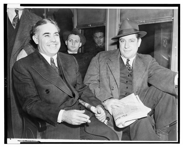 "[Louis Capone, left, and Emanuel ""Mendy"" Weiss holding a copy of the New York Times, three-quarter length portrait, seated] / World Telegram photo by Al Aumuller."