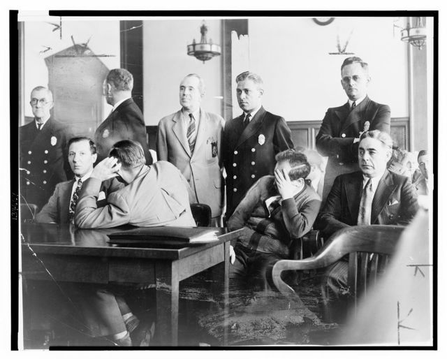 "[Louis ""Lepke"" Buchalter, facing front, seated with Emanuel ""Mendy"" Weiss and Phillip ""Little Farvel"" Cohen who shield their faces, and Louis Capone, in a Kings County Courtroom during jury selection] / World Telegram photo by Al Aumuller."
