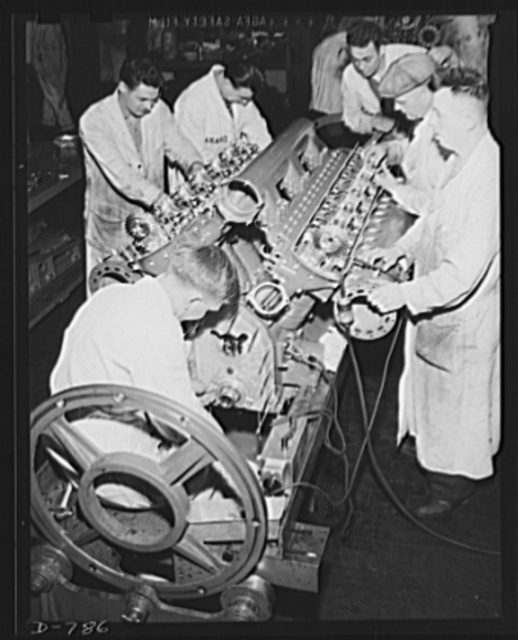 Machinists checking value clearance for timing with camshaft. This is one step in the assembly of a Packard marine engine. Packard marine engine plant, Detroit