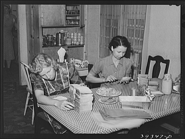 Maids making sandwiches for night shift workmen at Consolidated Aircrafts. This is in a boarding house for single men. They are given room and board--two meals every day and a lunch consisting of three sandwiches, fruit and cake for eight dollars weekly. While this house is clean and liked by the boarders, it is crowded and it is possible that it will be ordered to reduce the number of tenants by the public health officials. San Diego, California