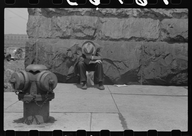 [Man seated on corner of Jefferson Street and Vernon Park Place, Chicago, Illinois]
