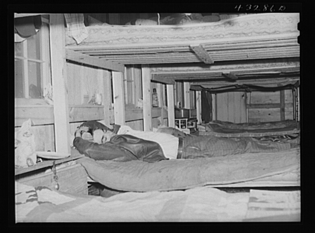 Man who works at Fort Bragg, North Carolina sleeping in a bunk house recently built to house thirty or forty men. There were only a few men left, most of them having been laid off had left. A few miles out of Fayetteville, North Carolina