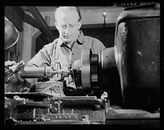 Man working on a lathe which is shaping precision instruments