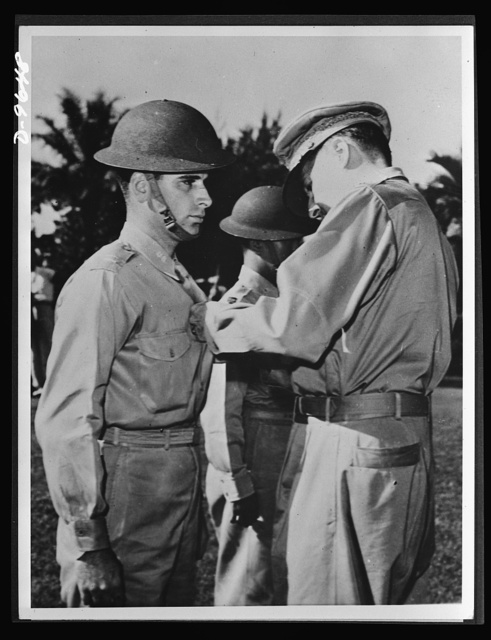 Manila, the Philippine Islands. For extraordinary heroism during attacks on Jap bridgeheads at Vigan, in Northern Luzon, Lieutenant Jack Dale of the U.S. Army Air Corps received a Distinguished Service Cross from General MacArthur (right) before Japanese forces forced American troop retirement from Manila. Other air heroes decorated with the Distinguished Service Cross were Captain Jesus A. Villamor (center rear) of the Philippine Army, and posthumously, Captain Colin P. Kelly, Jr., who bombed and sank a Jap battleship off Luzon. This picture, made December 22, 1941, was one of the last to leave the Philippines