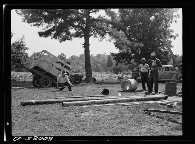 Measuring the well depth by using the old rope. Safe well demonstration near La Plata, Maryland. Charles County