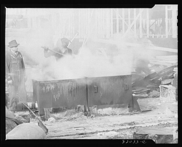 Melting tar for roofing on emergency defense office construction job. Washington, D.C.