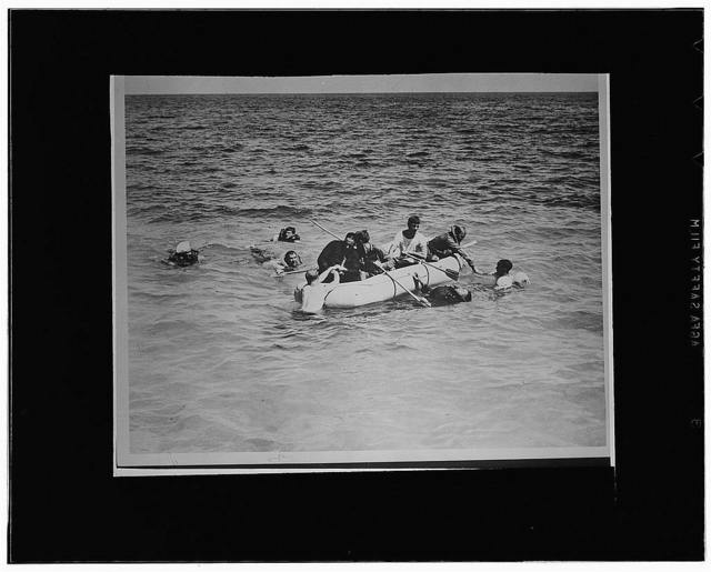 Men learning how to properly enter one of the life rafts on all PBY planes as part of a course in life saving and water safety for sailors at the naval operating base at Key West, Florida, under the supervision of C. Ben Stanton