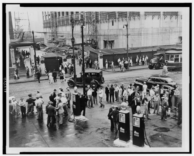 [Men milling around street across from the Brooklyn Navy Yard during an electrical workers strike; in background is a picket line] / World-Telegram photo by Al Ravenna.