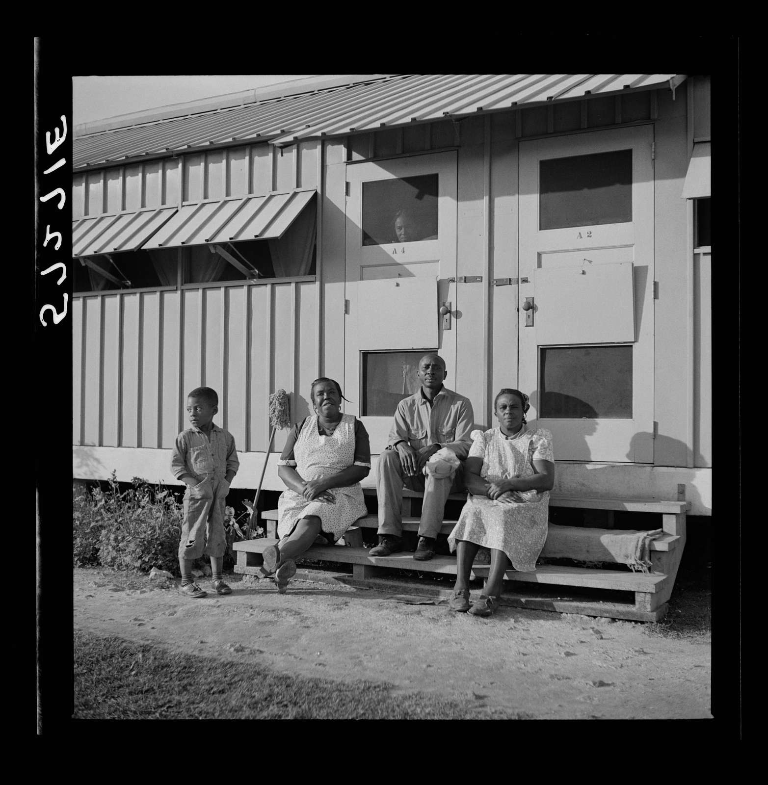 Migratory laborers sitting in front of their metal shelter at Okeechobee migratory labor camp. Belle Glade, Florida