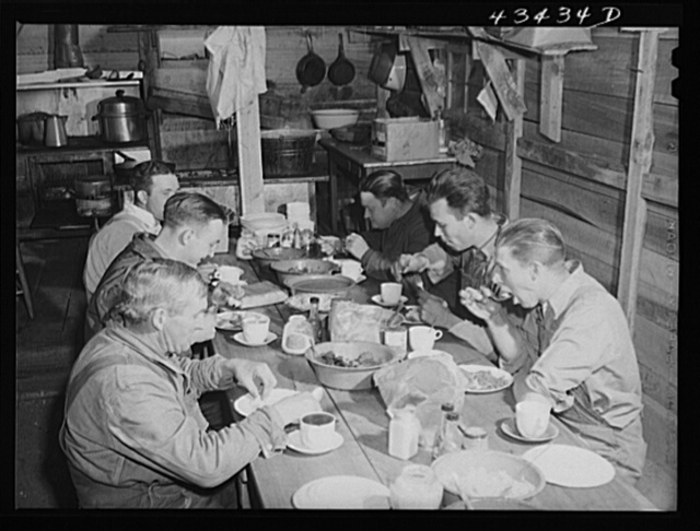 Migratory workers from Fort Bragg eating supper at a trailer settlement in Manchester, North Carolina