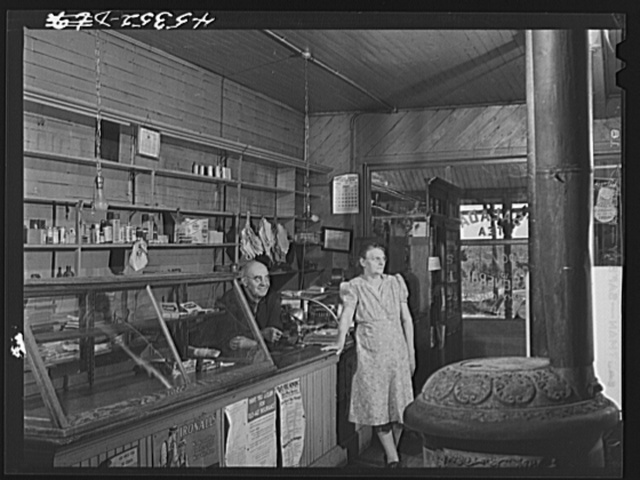 Mr. and Mrs. Merton Hoover in their store and post office in Sterlingville, New York. The Hoovers are moving out of the Pine Camp expansion area to a small house in West Carthage, New York