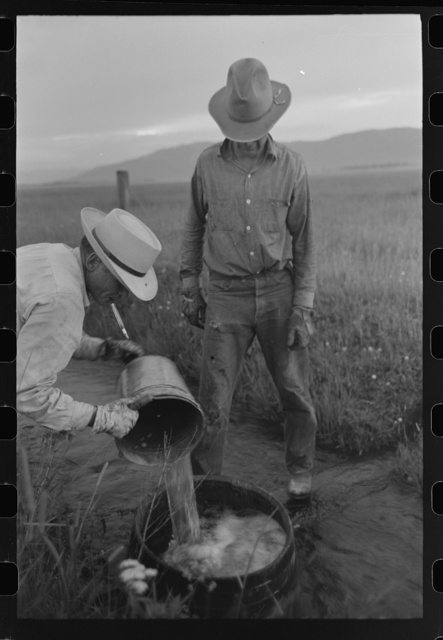Mr. Eddie Cruzen (with cigarette holder) and ranch hand mix up blue vitriol for treating hoof rot, Cruzen Ranch, Valley County, Idaho