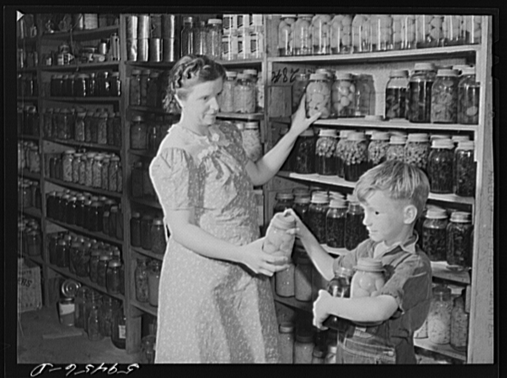 Mrs. Harvey Renninger and son in her home with canned goods. Two River Non-Stock Cooperative, FSA (Farm Security Administration) coop. Waterloo, Nebraska