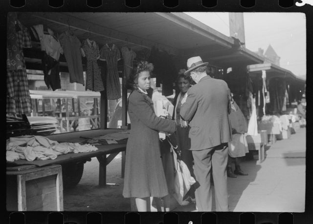 Negroes making purchases from white proprietor of street clothing stall, Black Belt, Chicago, Illinois