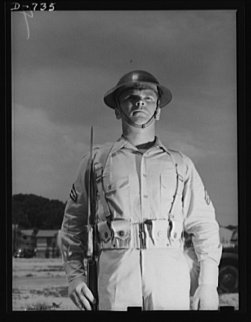 "New Army helmet. Corporal French L. Vineyard, Company M, 12th Infantry. Wearing combat pack, uniform, and old ""basin type"" helmet. Arlington Cantonment, Arlington, Virginia"