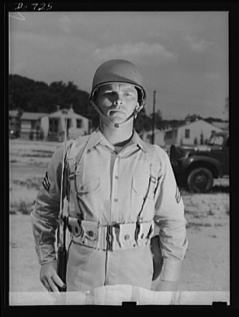 New Army helmet. Corporal French L. Vineyard, Company M, 12th Infantry, wearing a new Army helmet. Corporal Vineyard is wearing the combat pack and cartridge belt and is equipped with a Garand rifle with bayonet affixed