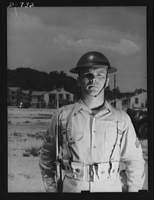 "New Army helmet. Corporal French L. Vineyard, Company M, 12th Infantry. Wearing combat pack and old ""basin type"" helmet. Arlington Cantonment, Arlington, Virginia"