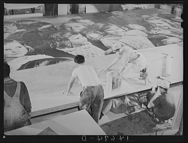 New York, New York. Preparing the defense bond sales photomural, designed by the Farm Security Administration, to be installed in the Grand Central terminal, in the shop of a contractor. Mounting the center panel on the homosote board with flour paste