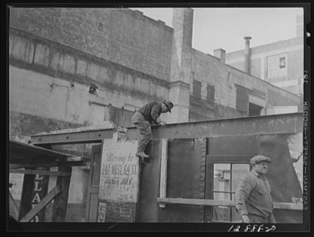 New York, New York. Workmen wrecking condemned buildings in the demolition of a slum area to make room for a housing project