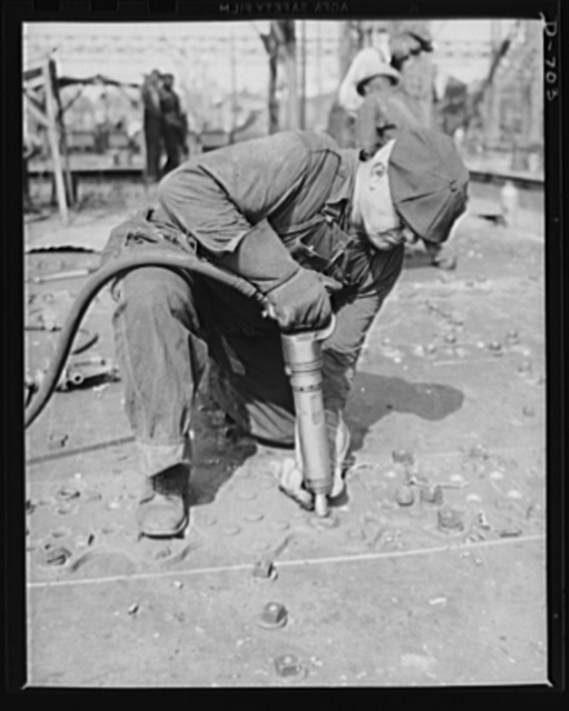 Newport News, Virginia. Riveter installing button-head rivets in a deck fitting of a C-3