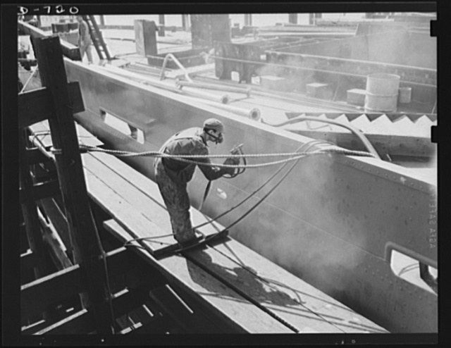 Newport News, Virginia. Spray painting the outside of the hull of a C-3. The section the worker is painting here is known technically as a deck thwart
