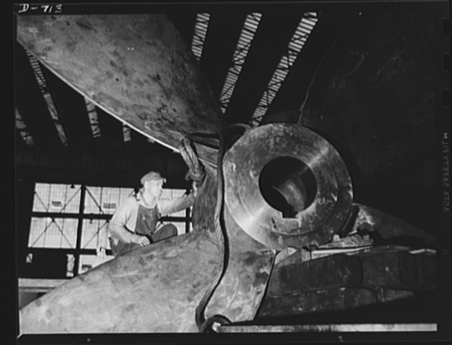 Newport News, Virginia. Worker attaching wire cable preparatory to lifting a cast propellor for a C-3. Formerly propeller blades were bolted on to the shaft, but today the propeller is cast in one piece