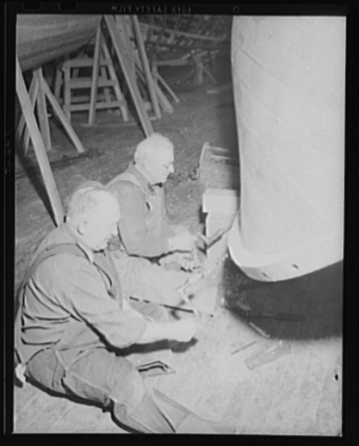 Not as easy as it looks. The men may be seated, but drilling boat holes in the keel of a Navy motor-launch is no child's play. The boat is under construction in the shipwright shop at eastern Navy yard