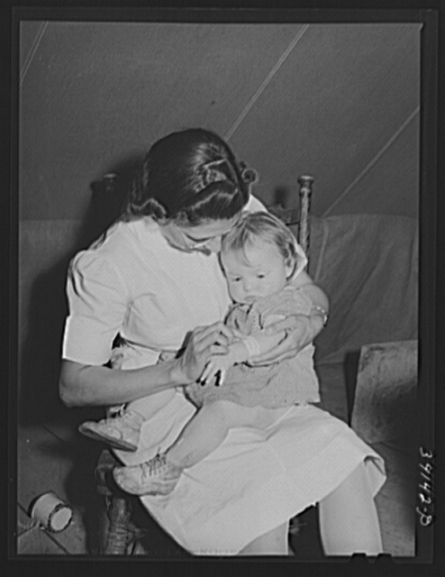 Nurse looks at cut on baby's arm at the FSA (Farm Security Administration) migratory labor camp mobile unit. Wilder, Idaho. The nurse not only is in attendance at the trailer clinic, but makes her regular rounds of calls to the tents