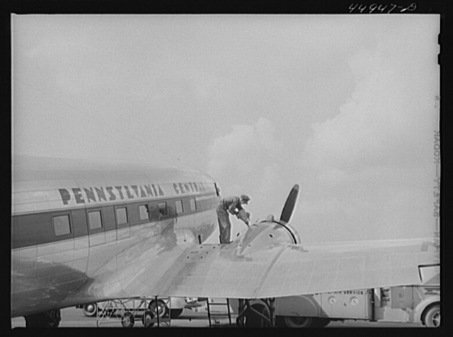 Oil for the engine of an airliner preparatory to takeoff. Municipal airport, Washington, D.C.