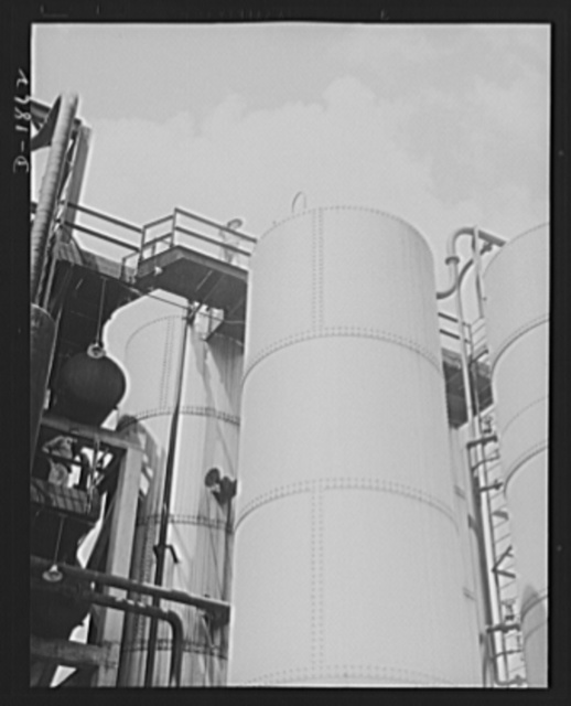 Oil. Vital operations in the refining of lubricants for the war machines of democracy are performed here. These are the solvent storage and surge tanks of the McKean plant of the Quaker State Refining Company, Bradford, Pennsylvania