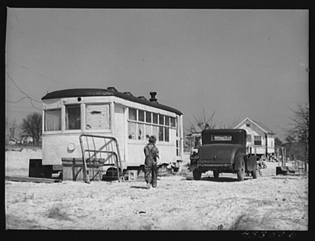Old street car converted into living quarters for family of four. They were born and raised in Fayetteville, but could not get a place to stay. Husband works at Fort Bragg, North Carolina. Just outside of Fayetteville, North Carolina