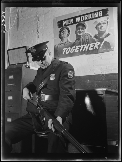 On guard against sabotage, this patrolman at a large defense production plant gives soldierly care to a rifle that may stop a saboteur. White Motor Company, Cleveland, Ohio