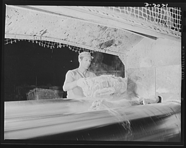 On the mill rollers. First the raw rubber is wedged into the revolving steel drums and mashed into a flat sheet which clings to one of the rollers like clothes sometimes stick to a clothes-wringer. Powders and liquids tossed into the center of this surging mass soon become a part of it. Firestone (General Tires), Akron, Ohio