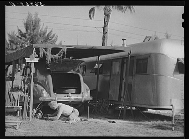 "One of the guests at Sarasota trailer park, Sarasota, Florida, washing his car. He has named his trailer home ""Loveless"""